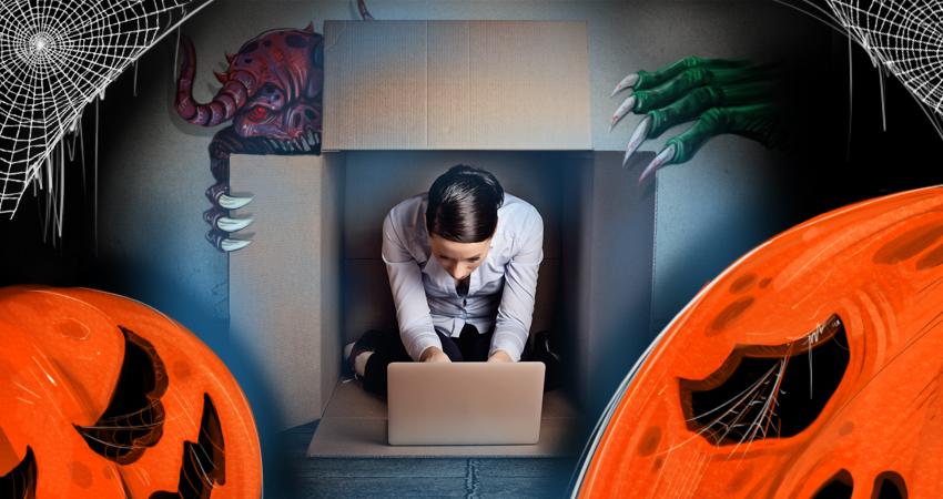 Mujer dentro de una caja utiliza el ordenador al lado de calabazas de Halloween