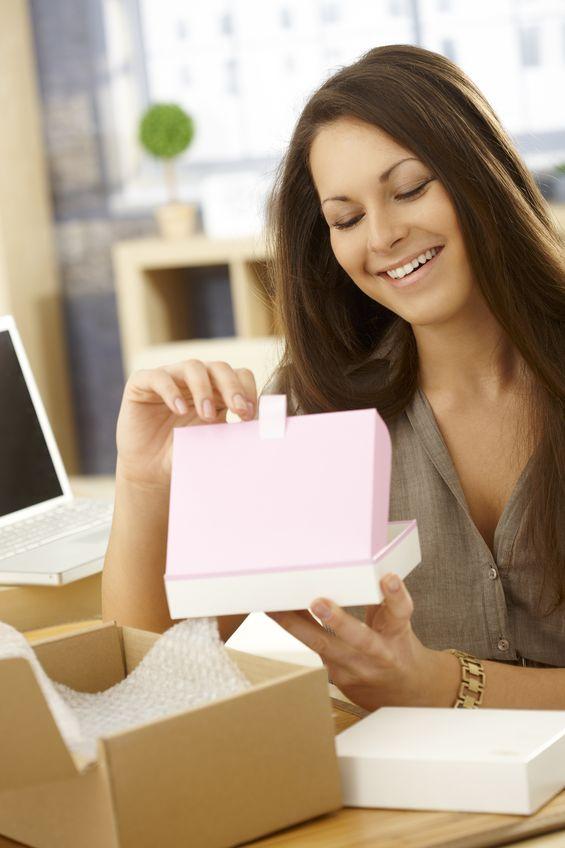 Mujer con el ordenador abre caja de suscripción sorpresa